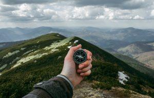Compass held in hand, overlooking mountain ranges