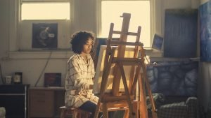 African-American woman sitting and painting - let long distance movers Charleston SC handle everything.