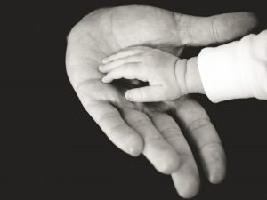 A man holding a baby's hand.