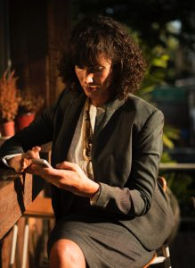 A businesswoman sitting at a bar looking at her phone