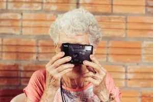 An older lady taking a photo with a vintage camera