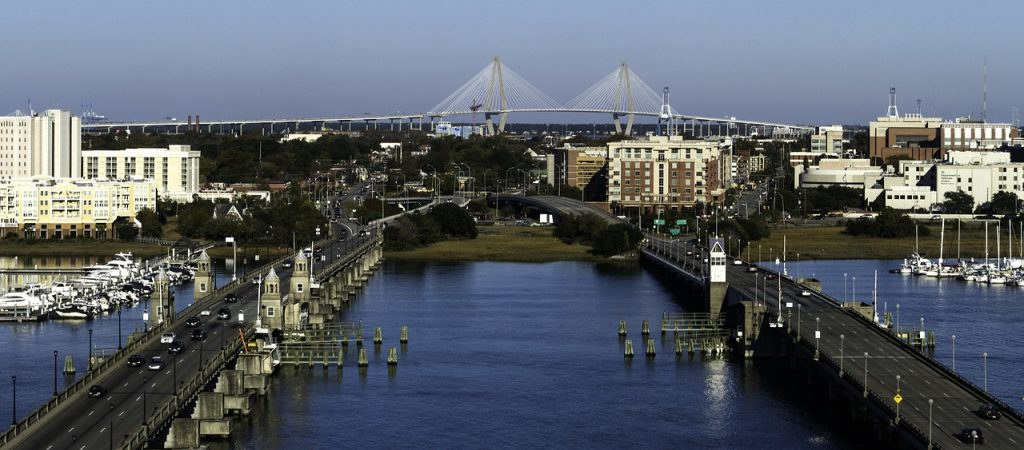 Charleston - one of the best places to retire in South Carolina; cityscape - a river, a bridge, buildings on both banks
