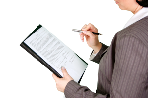 A woman holding some documents and a pen