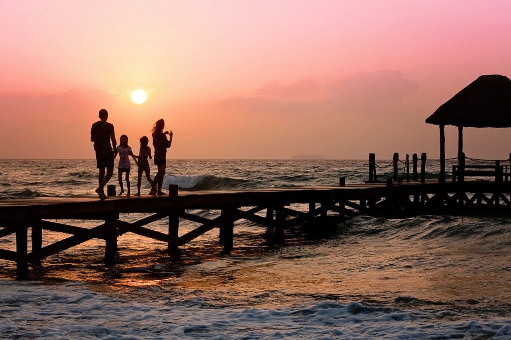 A family of four standing on a dock at sunset