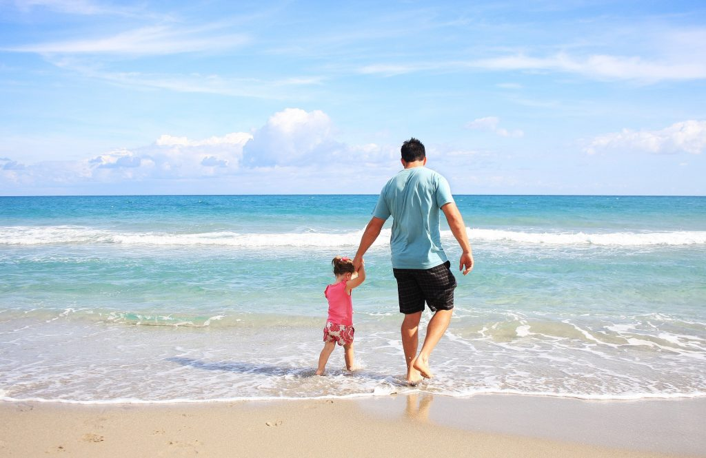 A man and a child on the beach.