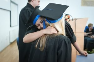 Two girls in caps and gowns hugging on graduation day, aiming towards finding a job in Sarasota