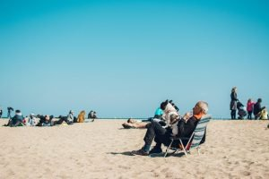 An older man resting on the beach with his dog sitting in his lap