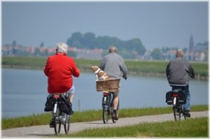Three elderly people riding bikes along the lake