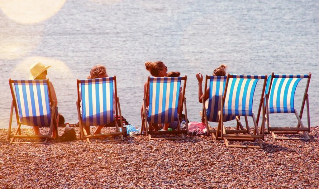 Four people sitting on the beach looking at the sea