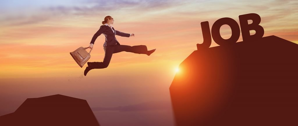 "A woman in a business suit jumping toward the word ""Job""."