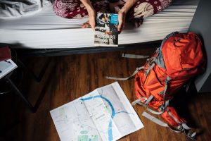 A girl sitting on a bed planning her trip.