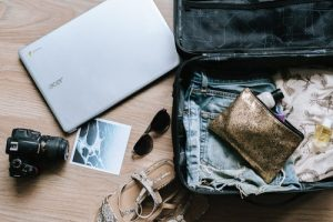 Laptop, sunglasses, clothes and shoes in suitcase