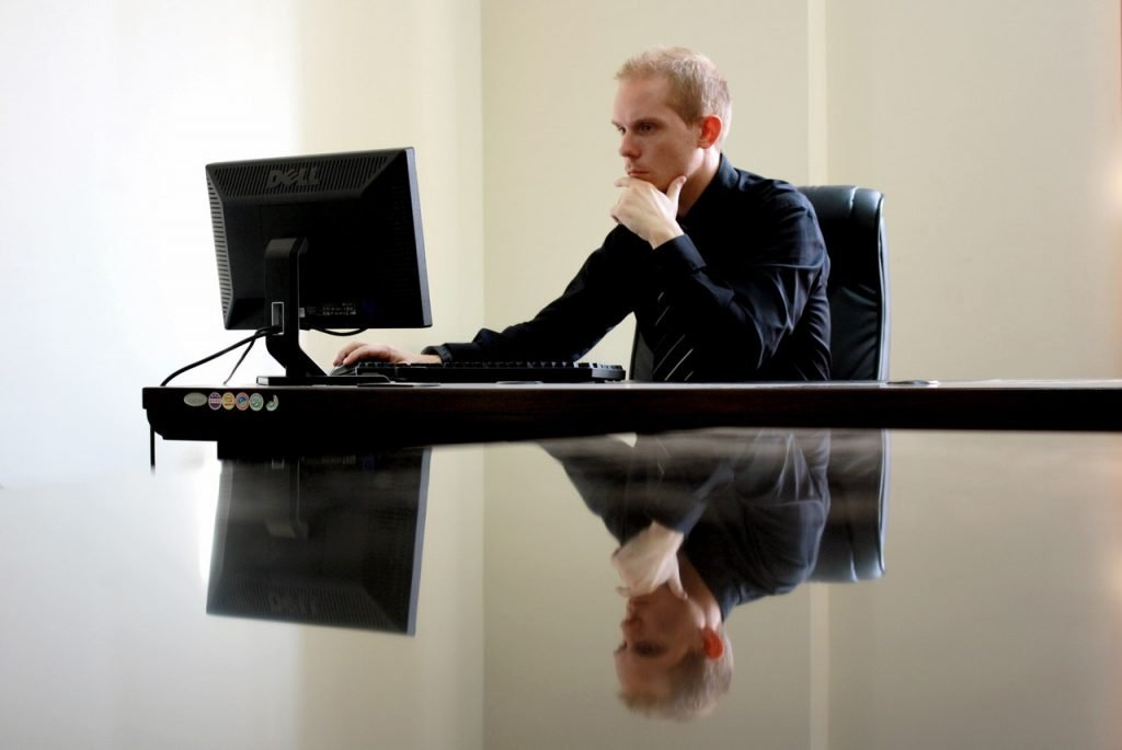 A man sitting in a desk chair working on his desktop computer