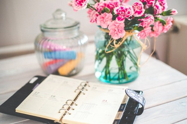A planner and pink flowers on the table.