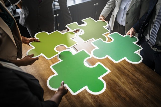 Four people holding four pieces of puzzle.