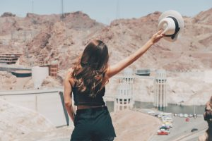 Interstate movers Nevada bring you to Hoover Dam. Women standing in front of it, holding the hat in one hand.
