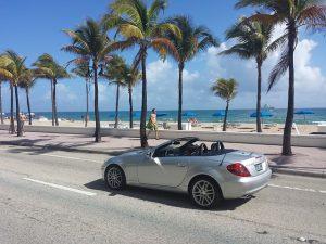 Silver car driving through Miami beach.