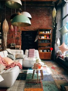 A vintage living room with couch and table, red brick wall