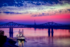 Boat, bridge, river and pink-purple sky