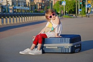 Kid sitting on a suitcase on the street