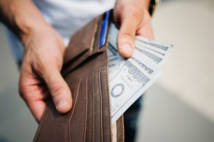 Man holding a wallet with cash