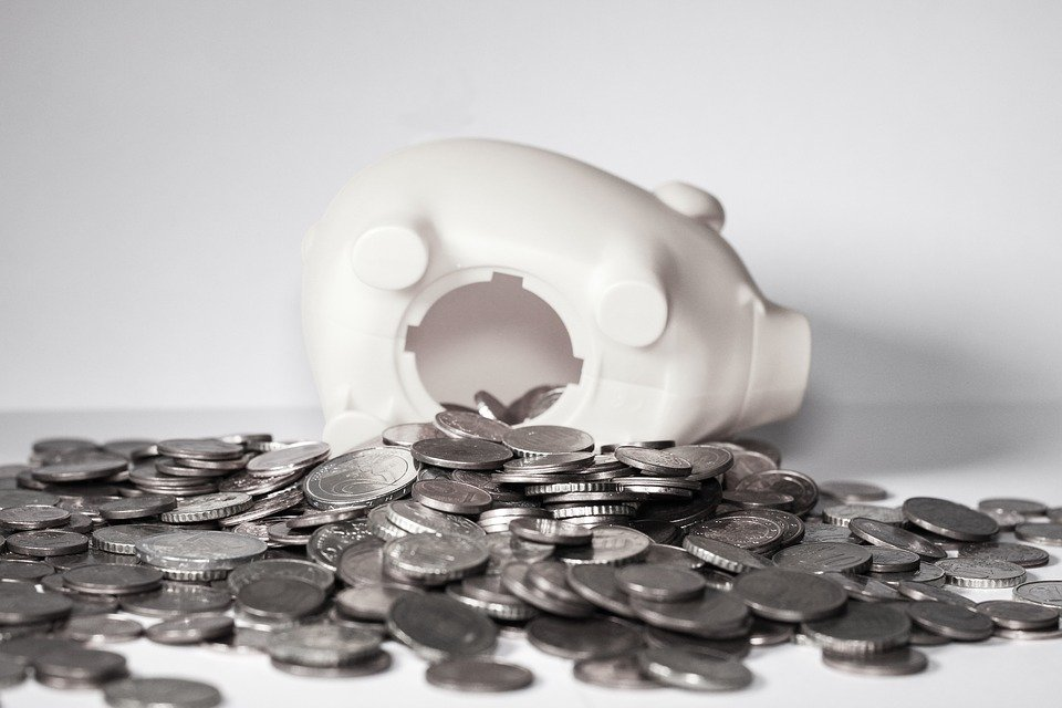 A white piggy bank with coins spilling out of it - finances are key to any coast-to-coast relocation checklist