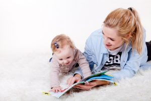 Woman and baby girl looking at the book