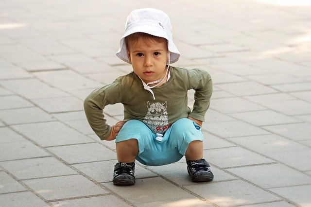 A kid squatting like you would when moving a stand-up piano.