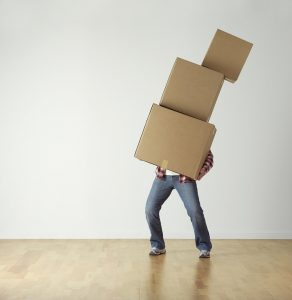Man carrying three boxes alone as one of the downsides of DIY moving