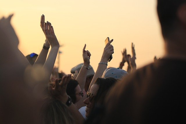 people in a festival with their arms up in the air