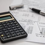 calculator and papers - calculating the main expenses of relocation