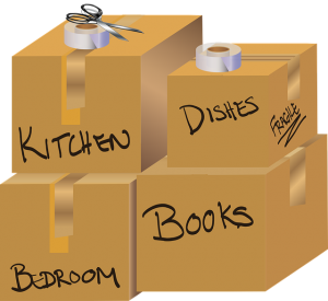 Packed belongings and box labeled according to rooms