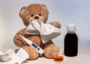 A teddy bear with a fever and some medicine