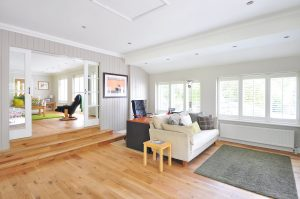 protect hardwood floor when moving bulky items by removing everything of the floor. A living room with a rug, sofa and a chair