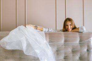 a woman standing behind the couch holding a white protective material