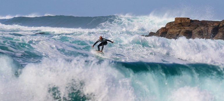 A person surfing after moving from Alaska to Hawaii.