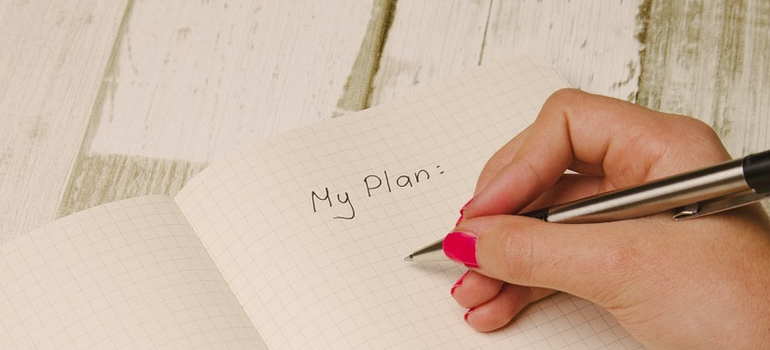 a person writing a plan of moving from Connecticut to North Carolina