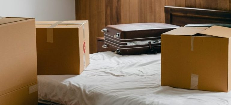 moving boxes and suitcase on the bed