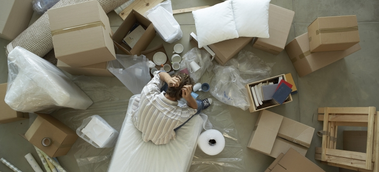 a man sitting between unpacked boxes