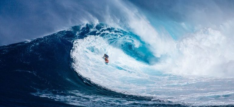 Man surfing after stress-free relocation with Honolulu interstate movers.