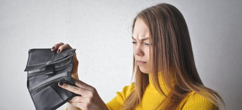 Woman frowning at her wallet.