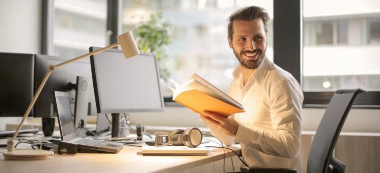 A man holding notes at his desk and smiling at work.