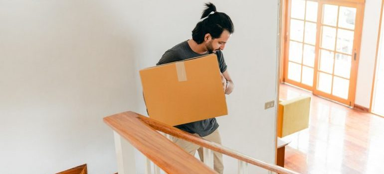 A man carrying a box down the stairs