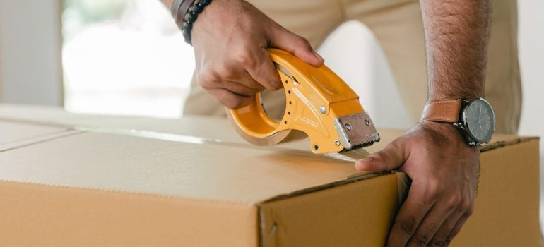man-taping-carrying-box-with-scotch