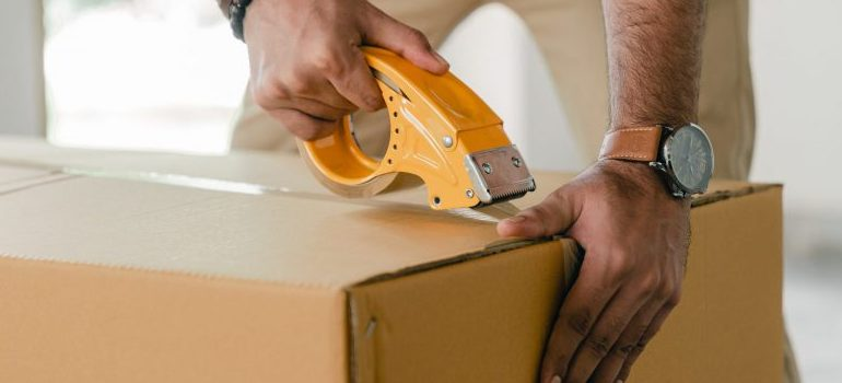 crop-man-taping-carrying-box-with-scotch