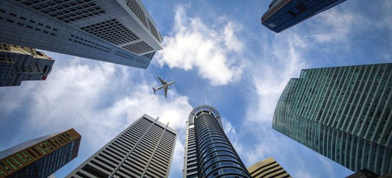 a picture of skyscrapers with an airplane above them
