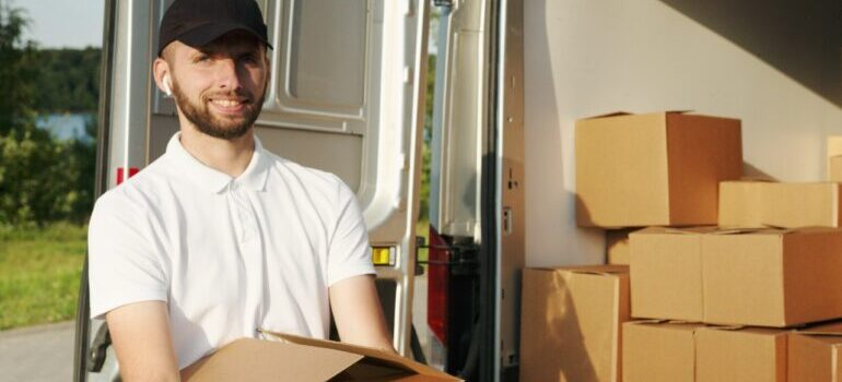 A mover smiling and carrying boxes