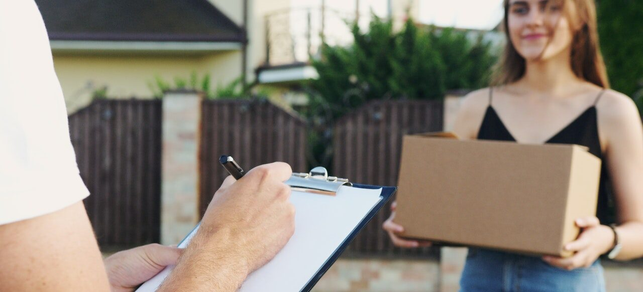 A mover with a clipboard and his client holding a moving box.
