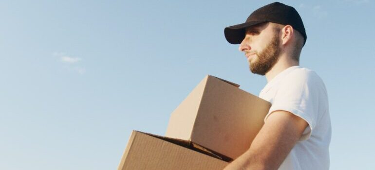 A man in a white shirt and a black cap carrying boxes.
