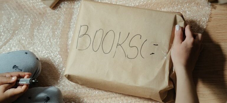 person wrapping books in packing paper